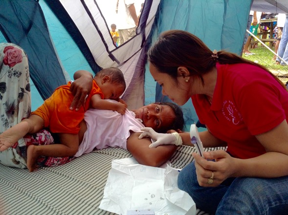 This mother of 10, a member of the Molbog tribe, receives a hormonal implant from midwife Mae Arzaga of Roots of Health, a Puerto Princesa-based women's health NGO. (Photo by Joie Cortina.)